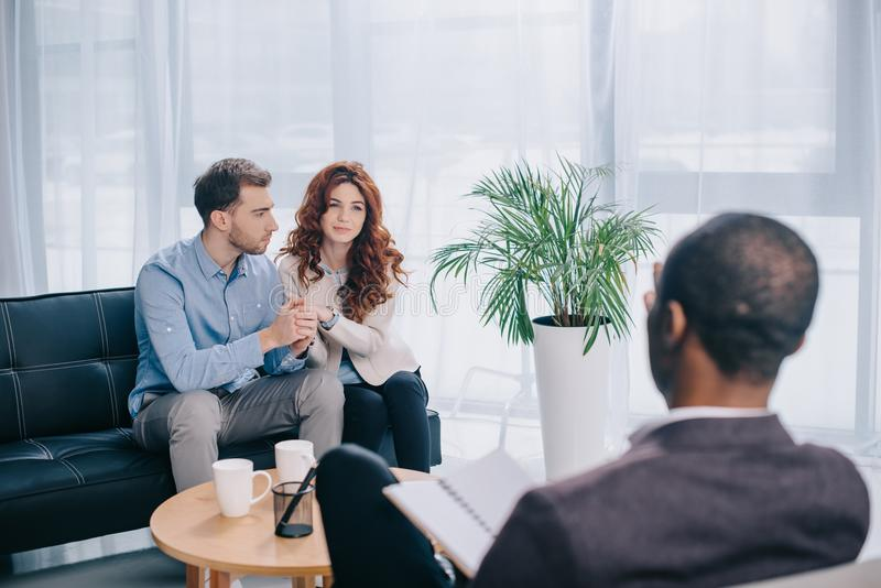 Young couple sitting on sofa in office and psychiatrist. With textbook royalty free stock photo