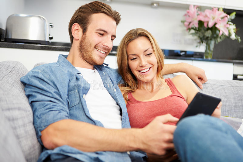 Download Young Couple Sitting On Sofa Using Digital Tablet Stock Photo - Image: 40095374