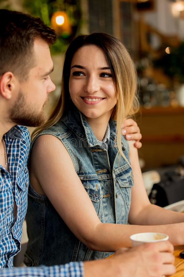 Couple sitting at a table in a cafe and drinking coffee stock photo