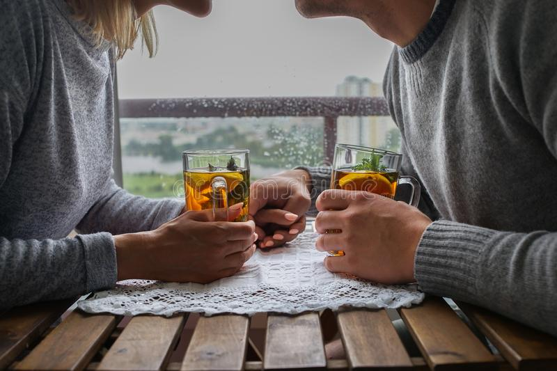 Young couple sitting at a table, with the care relate to each other in the rain outside the window. warm relations on a royalty free stock image