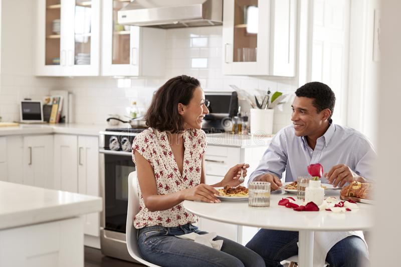Young couple sitting at the table in their kitchen eating a romantic meal together, selective focus stock images
