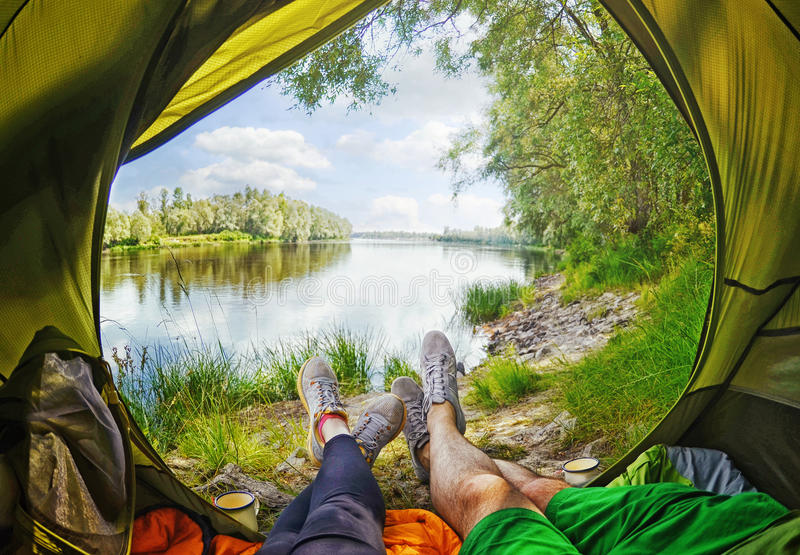 Young couple sitting in the tent while looking on the Desna river stock photo