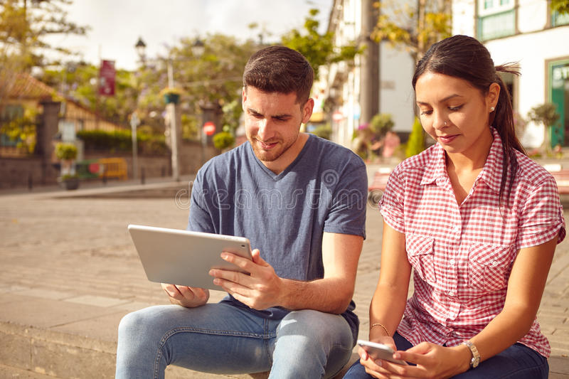 Young couple sitting in a town square. On a bench looking at a tablet and a cell phone while dressed casually in jeans and t-shirts stock images
