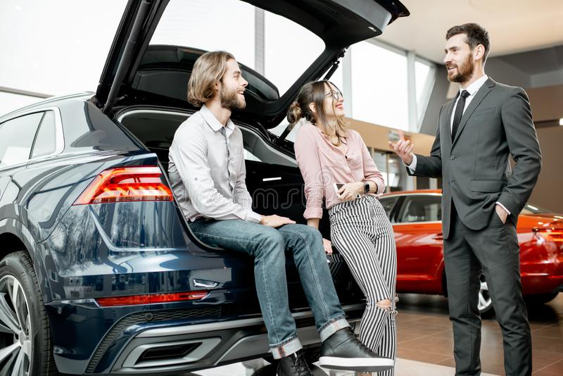 Couple with salesperson on the back of a new car in the showroom stock photos