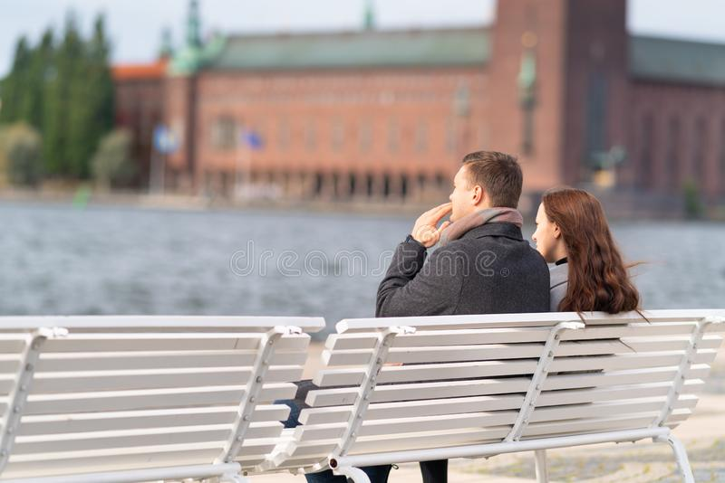 Young couple sitting on a waterfront bench royalty free stock image