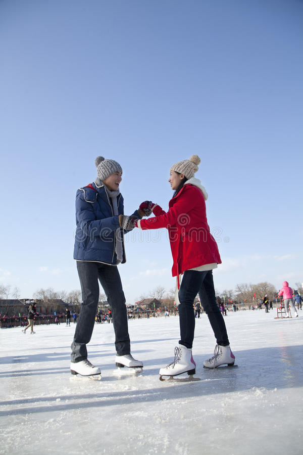 Young couple skating at ice rink stock photos