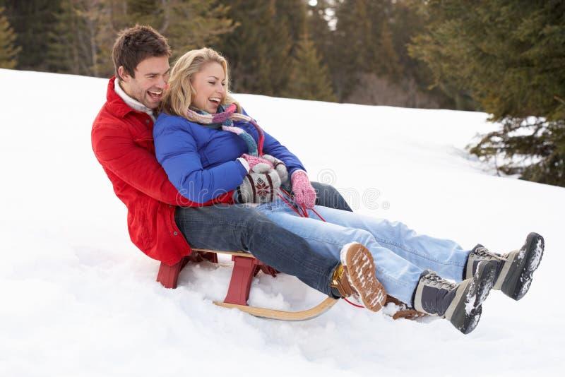 Young Couple Sledding stock photos