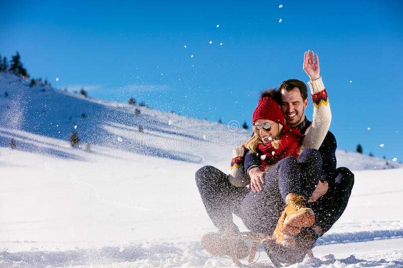 Young Couple Sledding And Enjoying On Sunny Winter Day.  royalty free stock photography