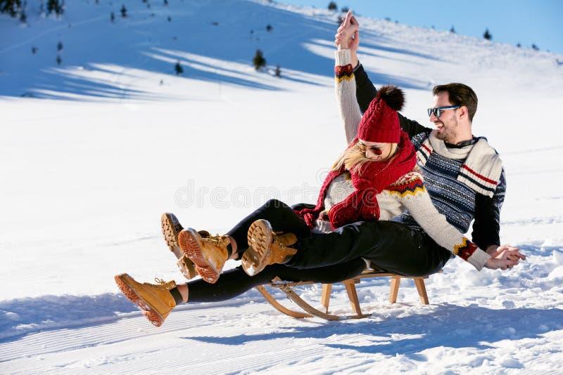 Young Couple Sledding And Enjoying On Sunny Winter Day.  royalty free stock photo