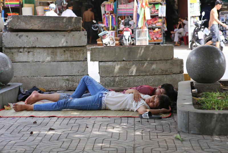 A young couple sleep on the streets of Hanoi in each other's arms royalty free stock images