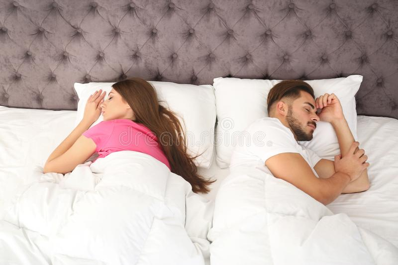 Young couple sleeping back to back at home. Relationship problems stock photography