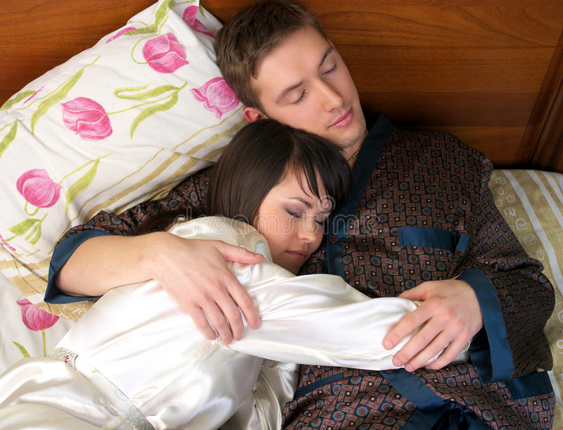 Young couple sleeping in the bed royalty free stock photos