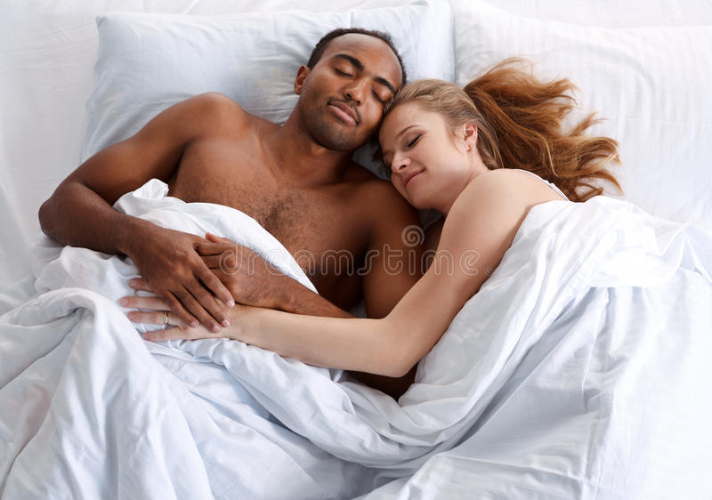 Young couple sleeping on the bed in bedroom. stock photography