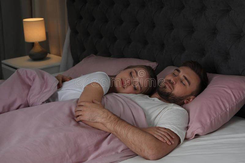 Young couple sleeping together in bed royalty free stock photography