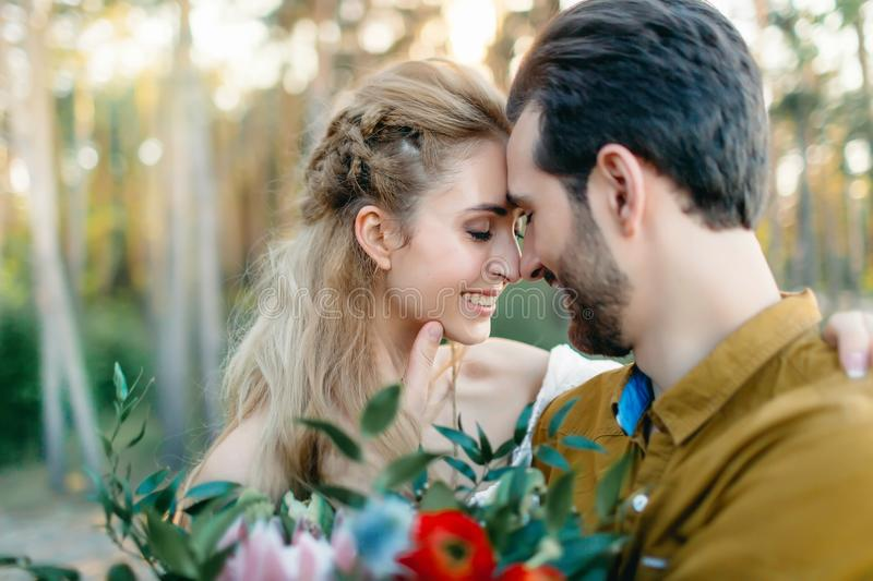 A young couple smile and touching foreheads. Autumn wedding ceremony outdoors. Bride and groom look at each other with royalty free stock photography