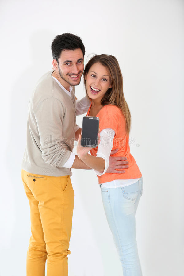 Young couple smiling and showing smartphone. Cheerful young couple showing smartphone royalty free stock photography