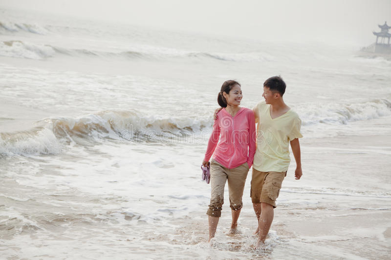 Young couple smiling and walking by the waters edge on the beach, China stock photography