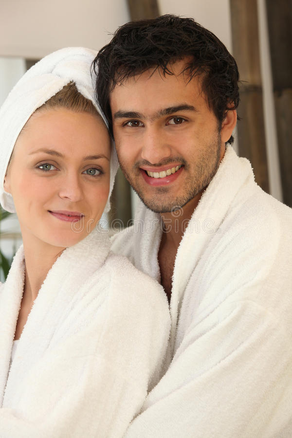 Young couple smiling wearing bathrobe stock image