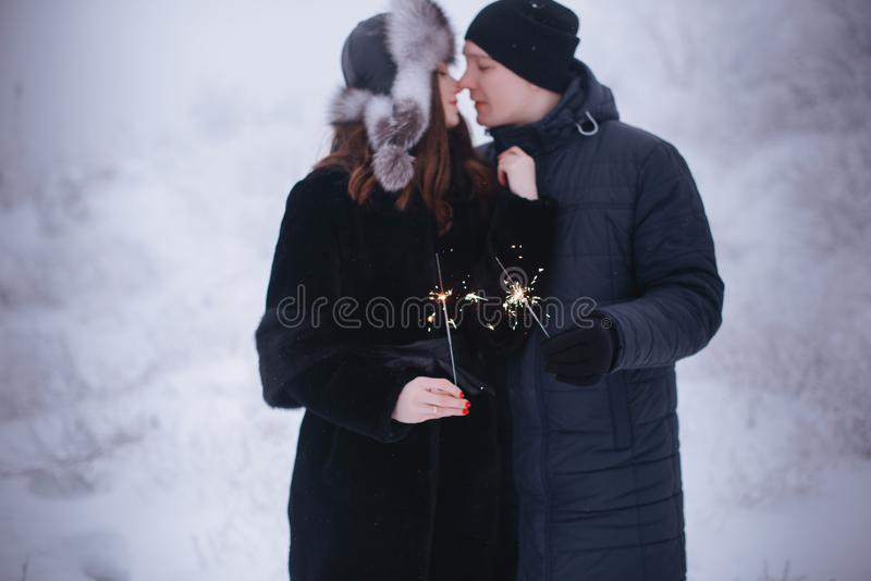 Young couple with sparklers in winter forest. Smiling family with bengal lights. royalty free stock image