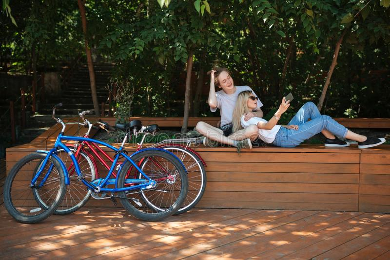 Young couple spending time in park with red and blue bicycles nearby. Boy sitting on bench in park with beautiful girl royalty free stock image