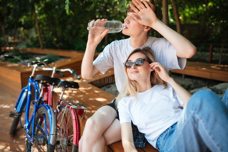 Young couple spending time in park with two bicycles nearby. Boy sitting on wood bench and drinking water with beautiful stock photos