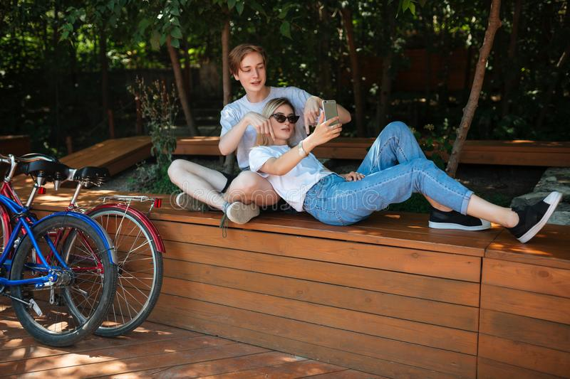 Young couple spending time together in park with bicycles nearby. Boy sitting on bench in park with pretty girl with stock photography