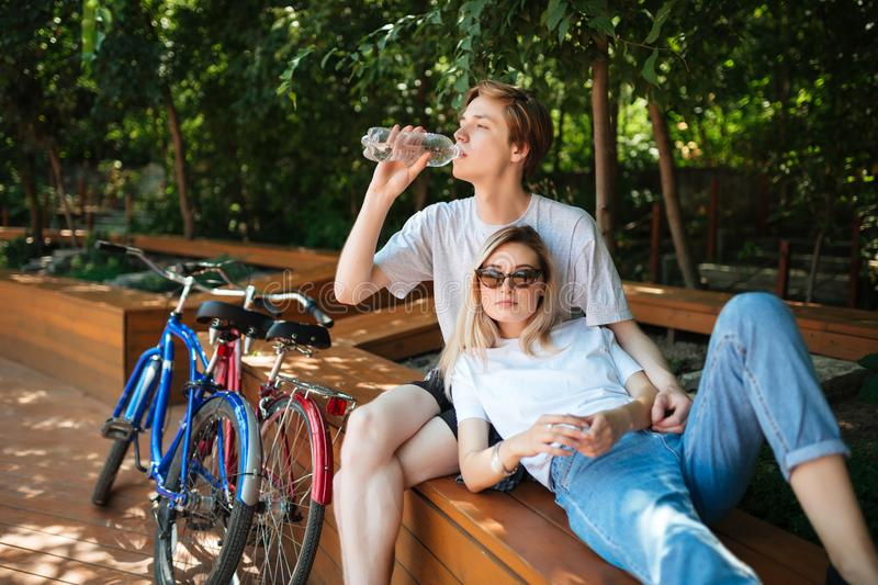 Young couple spending time on wood bench in park with two bicycles nearby. Boy sitting on bench and drinking water with royalty free stock photography