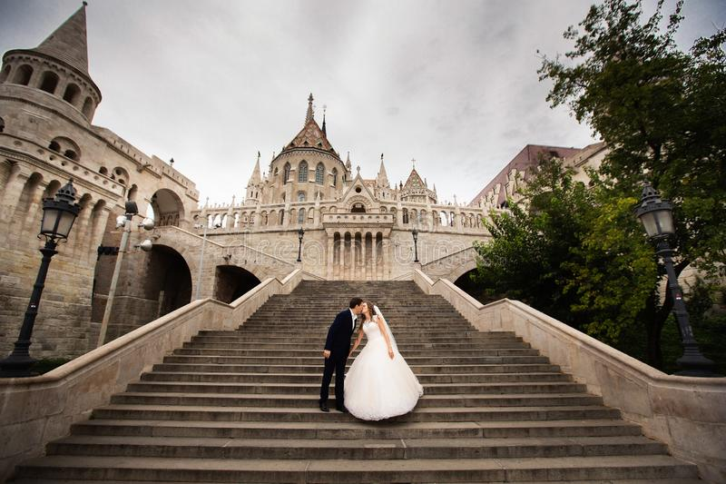 Young couple on the stairs on the background of the architecture of the Bastille Fisherman royalty free stock photo