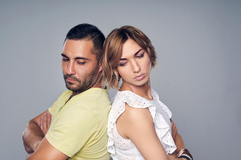 Young couple standing back to back with expression of sadness royalty free stock image