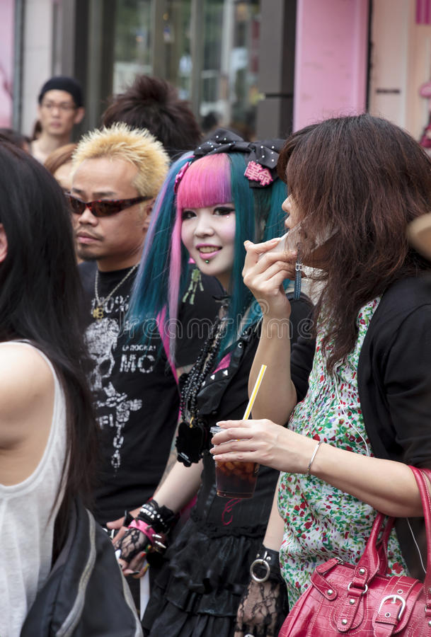 A young couple standing in the crowd in Harajuku di. Tokyo, Japan - June 2010 - A young couple standing in the crowd in Harajuku district in June 2010 in Tokyo royalty free stock image