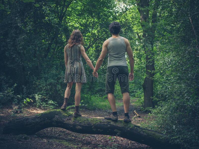Young couple standing on a log in the forest royalty free stock photography