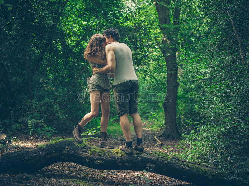 Young couple standing on log kissing royalty free stock images