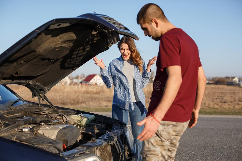 Young couple standing near broken car, swear in front of opened hook, male tries to repair vehicle and his wife shouts loudly, stock photos