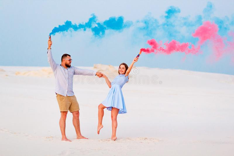 Young couple standing on a sand and holding colored smoke bomb , romantic couple with blue color and red color smoke bomb on stock images