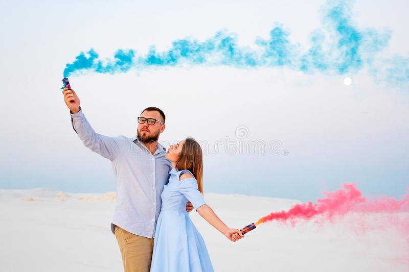 Young couple standing on a sand and holding colored smoke bomb , romantic couple with blue color and red color smoke bomb on beac. H royalty free stock photo