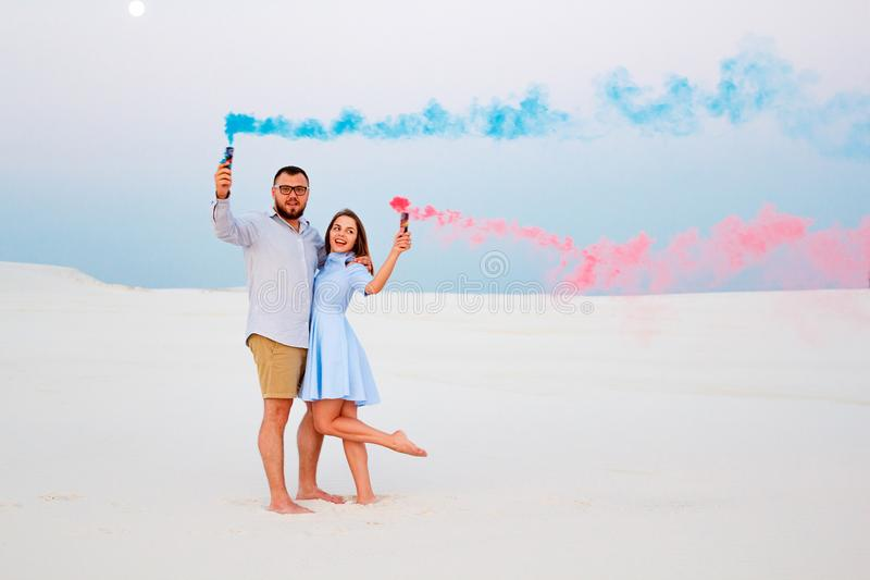 Young couple standing on a sand and holding colored smoke bomb , romantic couple with blue color and red color smoke bomb on beac. H stock image