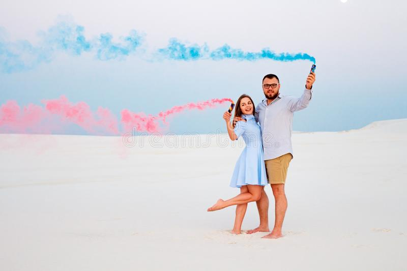 Young couple standing on a sand and holding colored smoke bomb , romantic couple with blue color and red color smoke bomb on beac. H royalty free stock photos