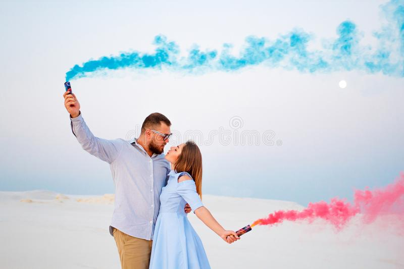 Young couple standing on a sand and holding smoke bomb and looking at each other, romantic couple with blue color and red color s. Moke bomb on beach stock photos
