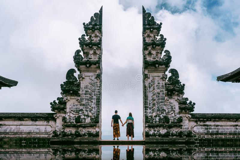Young couple standing in temple gates and holding hands of each other at Lempuyang Luhur temple in Bali, Indonesia. Vintage tone stock photo