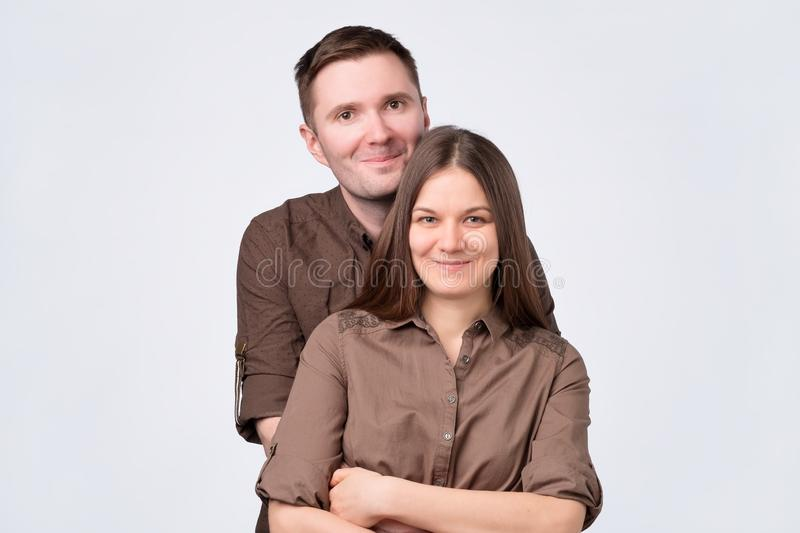 Young couple standing on white background, hugging smiling at camera royalty free stock photos