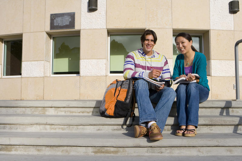 Young couple on steps studying, smiling, portrait, low angle view royalty free stock photos