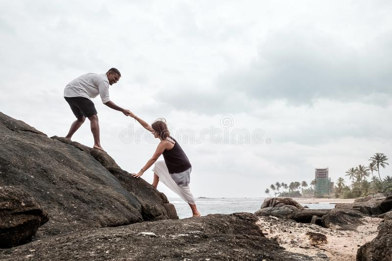 Young couple on the stone near ocean royalty free stock photos