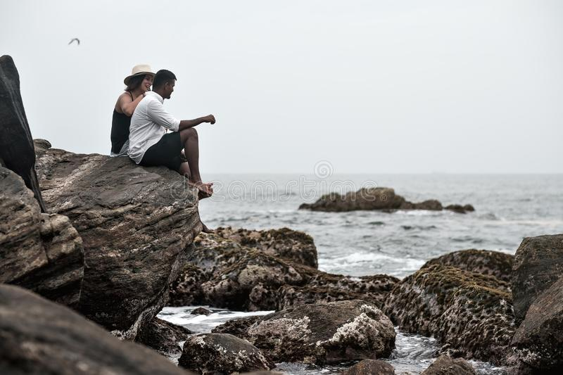 Young couple on the stone neat ocean stock photos