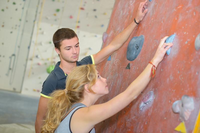Young couple stood by indoor climbing wall stock images
