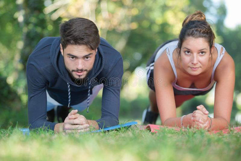 Young couple strengthening their muscles in park stock photos