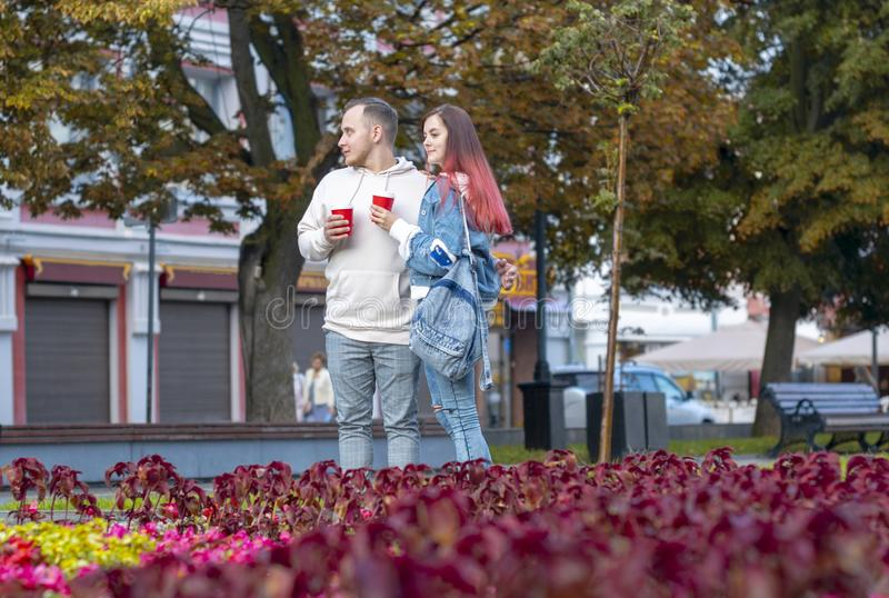 A young couple of students in love - a beautiful girl and a nice guy on the street with cups of coffee in the summer. royalty free stock photography