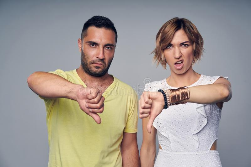 Young couple in studio standing with expression of disgust. Gesturing thumb down, over grey background royalty free stock image
