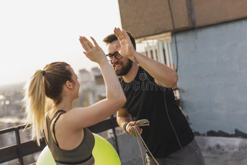 High five after a successful workout. Young couple after a successful workout standing on a building rooftop terrace, giving each other high fives stock photography