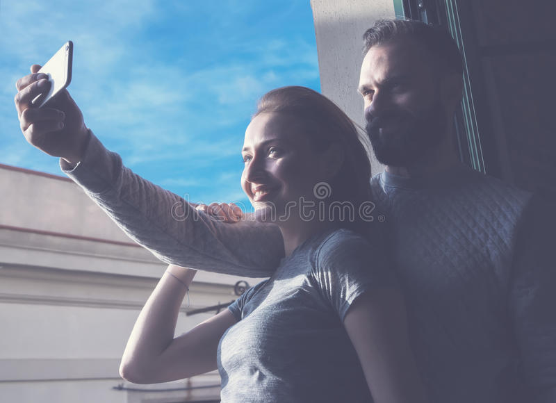 Young couple summer holiday city. Photo woman and bearded man making selfie mobile phone in modern loft. Using stock photo