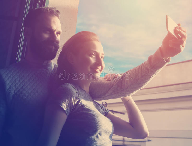 Young couple summer holiday city. Photo woman and bearded man making selfie mobile phone in modern loft. Using royalty free stock photos